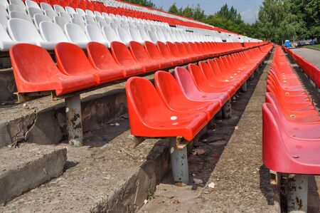 Empty seats in the stands of the arena. Rows of red and white stadium seats without spectators. The concept of the abolition of sports and mass entertainment events Zdjęcie Seryjne