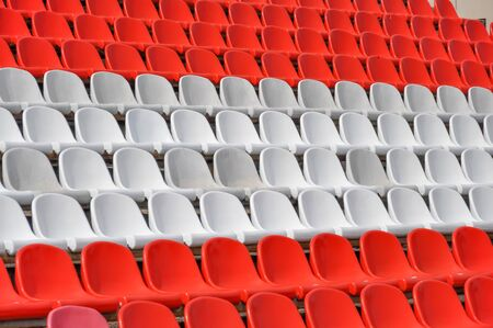 Empty seats in the stands of the arena. Rows of red and white stadium seats without spectators. The concept of the abolition of sports and mass entertainment events Foto de archivo