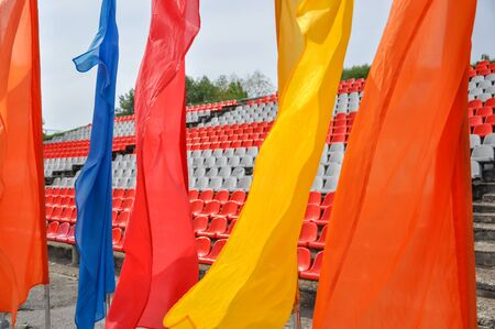 Colorful waving flags and empty seats in the stands of the arena or auditorium. Rows of red and white stadium seats without spectators. Concept of cancellation of mass sports and entertainment events