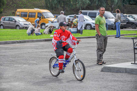 Cheboksary, Russia-August, 19, 2012. A young boy dressed in red hockey gear and a baseball cap rides a Bicycle on a summer day in a Park against the background of a Parking lot