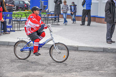 Cheboksary, Russia-August, 19, 2012. A young boy dressed in a Red hockey uniform and a baseball cap rides a Bicycle on a summer day on a city street Publikacyjne
