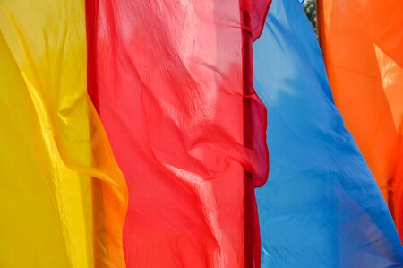 Bright multicolored vertical flags fly on flagpoles on a Sunny, windy day. Photo close up Zdjęcie Seryjne