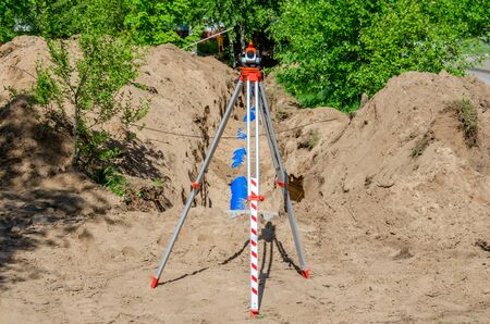 A construction site among trees with a trench in the sandy ground with a blue plastic pipe and a theodolite in the foreground