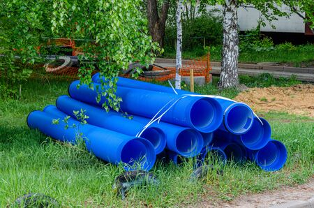 Blue plastic pipes and concrete rings used on the construction site. Double-layer blue PVC water pipes unpacked for installation.