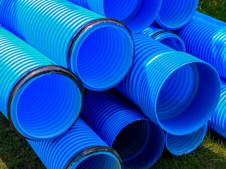 Blue corrugated polypropylene pipes used on the construction site. Double-layer blue PVC water pipes unpacked for installation. Close up