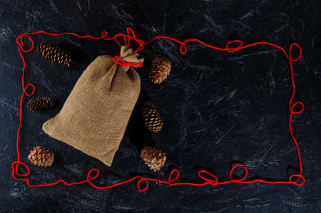 Christmas bag made of coarse burlap, cones, Christmas decorations, frame made of red twine on a dark background, space for text. Copy space. Stockfoto