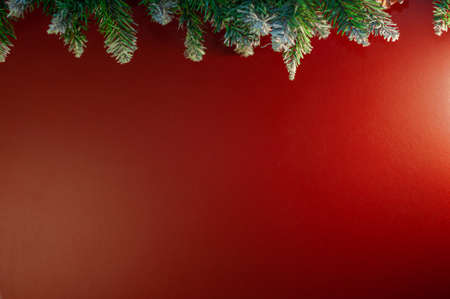 Christmas garland with green fir branches and cones on the background of a red wall with space for text. Copy space. Shallow depth of field and selective focus. Stok Fotoğraf