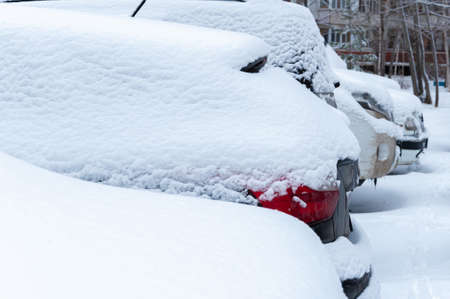 Cars covered with a thick layer of snow in a snow-covered street Parking lot in a residential area of the city