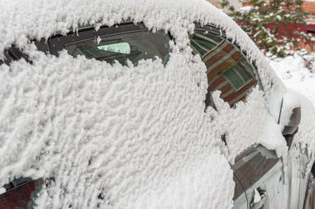 Close-up of the side Windows of a car covered with a thick layer of snow in a street Parking lot in a residential area of the city Stock Photo