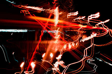 High-speed radial light paths of city lights and car headlights on the road, highway in the night city, long exposure, abstract urban background.
