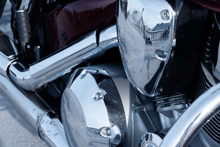 A modern powerful road bike with a shiny chrome reflective engine surface with exhaust pipes in the street parking lot.