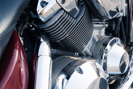 Close-up of a powerful motorcycle engine block with chrome-plated parts and reflective surfaces.