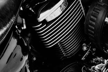 Powerful motorcycle engine block with chrome details and reflective surfaces, black and white close-up.