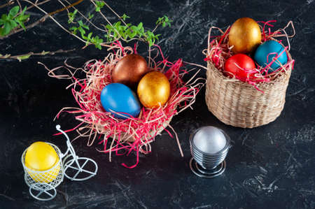 Homemade multicolored painted Easter eggs on multicolored straw in wicker baskets and in stands on a dark background, Easter decoration, top view