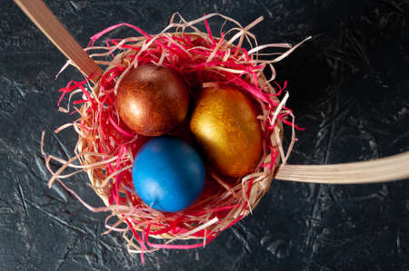 Homemade multicolored painted Easter eggs on colorful straw in a wicker basket on a dark background
