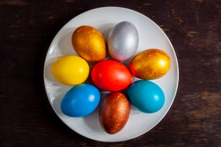 Homemade colorful painted Easter eggs on plates on a dark wooden background.