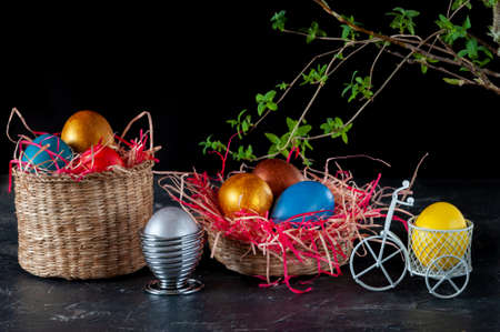 Homemade multicolored painted Easter eggs on colorful straw in wicker baskets and in stands on a dark background, Easter decoration