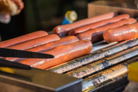 Hot dog sausages are fried on a rotary cooking machine in an outdoor cafe Stok Fotoğraf