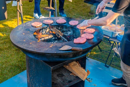 On the lawn, a large round wood-burning grill is roasting beef patties for burgers. Barbecue festival in the city park. Street fast food.
