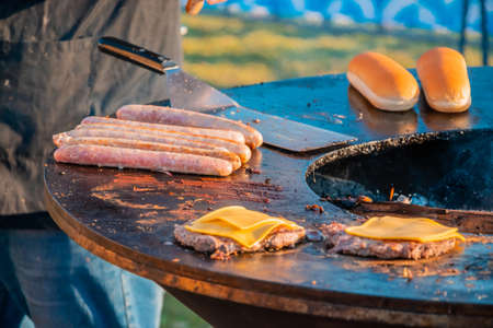 On the lawn, a large round wood-burning grill is roasting beef patties for burgers. The cook turns over the fried cutlets. Barbecue festival in the city park. Street fast food.