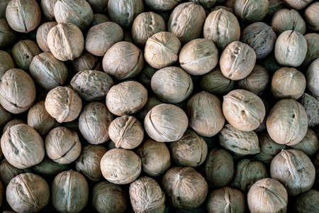 A pile of walnuts, a close-up walnut counter in a farmer's market. Copy space.