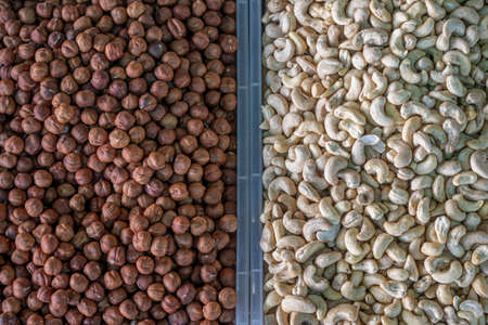 A pile of cashews and hazelnuts, a stall with cashews and hazelnuts close-up at the farmer's market. Copy space.