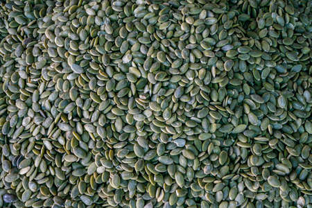 A pile of peeled pumpkin seeds, a stand with pumpkin seeds in close-up at the farmer's market. Copy space. Stok Fotoğraf
