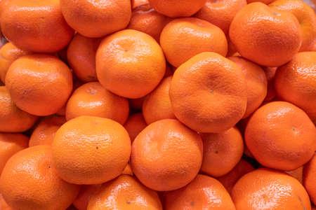 Fresh citrus tangerines, mandarins pile close-up in farmer's market
