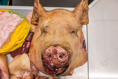 Head and legs of a pig on the counter of a butcher shop in a farmer's market, butchered pig carcass close-up.