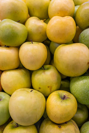 Fresh ripe yellow apples on the counter of a farm shop