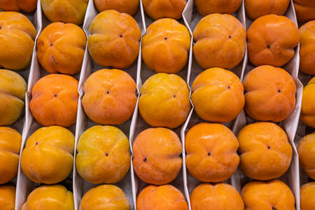 Fresh persimmon, a tray of ripe juicy persimmons close-up at the farmer's market Stok Fotoğraf