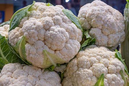 A pile of cauliflower, a tray of ripe cauliflower heads close-up at a farmer's market