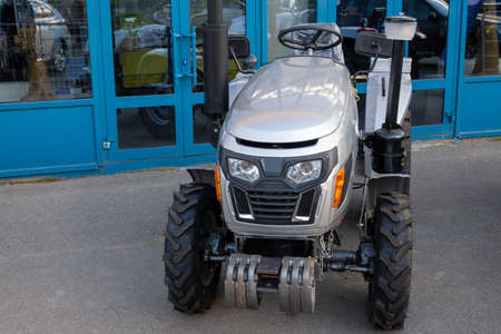 New mini tractor in the parking lot at the entrance to the farmers ' market, equipment for agricultural work. Stok Fotoğraf