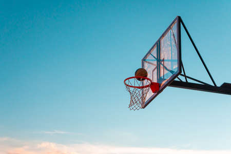 A basketball basket with a ball on a blue sky background. Transparent plastic basketball shield on the outdoor basketball court. Stok Fotoğraf