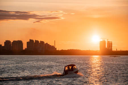 Silhouettes of city buildings on the shore against the background of the setting sun and glare on the water. Sunset on the river, a motor boat crossing a sunny path on the water.