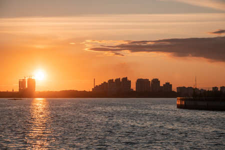 Silhouettes of city buildings on the shore against the background of the setting sun and glare on the water. Sunset on the river. Stok Fotoğraf