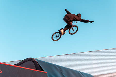 Bmx rider doing trick on ramp in skate park. Sports, extreme sports, freestyle, the concept of outdoor activity.
