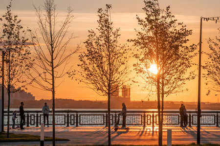 Silhouettes of people walking along the embankment against the background of the setting sun and glare on the water. Sunset on the city promenade.