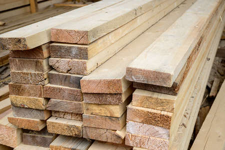 Piles of wooden planks at the sawmill for the manufacture of cladding. Warehouse of boards in the open air for the construction of houses. Timber in stacks, construction materials industry.