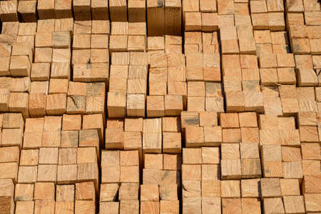 Piles of wooden planks at the sawmill for the manufacture of cladding. Warehouse of boards in the open air for the construction of houses. Timber in stacks, construction materials industry. Stock Photo