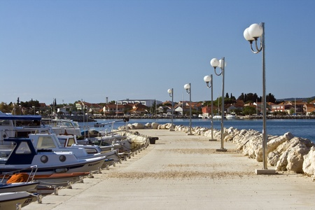 Pier, port with berthed boats and street lamps in Bibinje