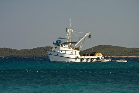 trawler: Aquamarine, white and green presenting white fishing boat Editorial