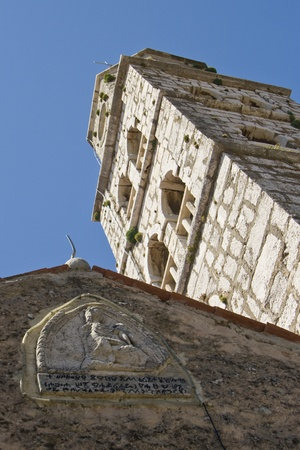 patron: Stone releif on a buildings and the church tower