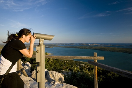 Woman looking through the telescope on te Vrana lake and islands Stock Photo - 10274462