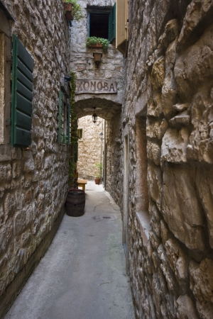 Narrow stone alley with a wooden konoba sign in Vodice photo
