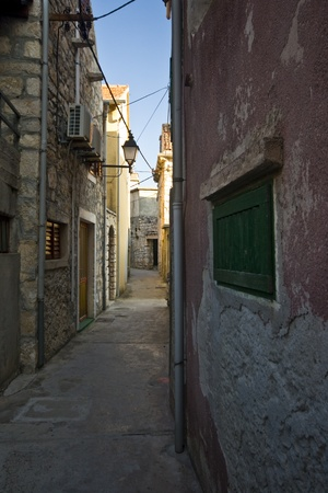 vegatation: Stone houses and street of island Krapanj, the smallest inhabited island of the Adriatic sea. It is also the most densely inhabited island and has the lowest elevation of 1.5 m above sea level. Stock Photo