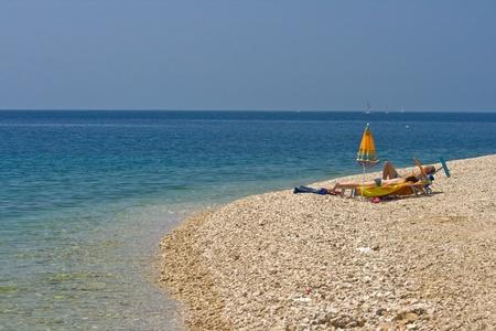 People sunbathing on the pebble beach of Primosten