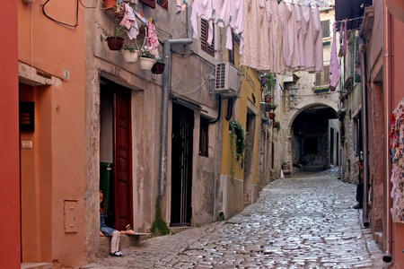 Stonepaved Garzotto street in Rovinj with the medival buildings and arch Stock Photo - 10519358