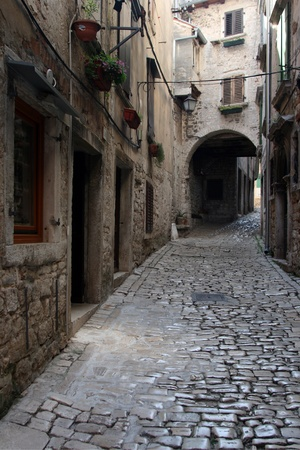 carrera: Stonepaved Garzotto street in Rovinj with the medival buildings and arch
