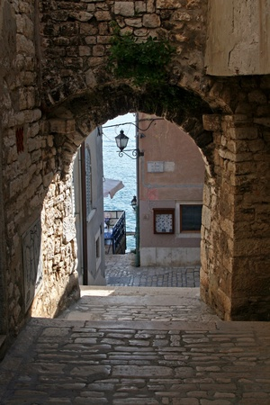 lamp made of stone: Arch and stonepaved alley by the coast in Rovinj Editorial